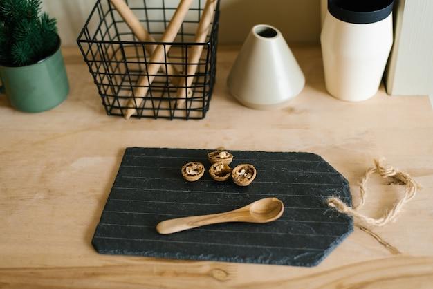Walnoten op een leisteen zwarte snijplank en een houten lepel op het aanrecht in de keuken scandinavisch