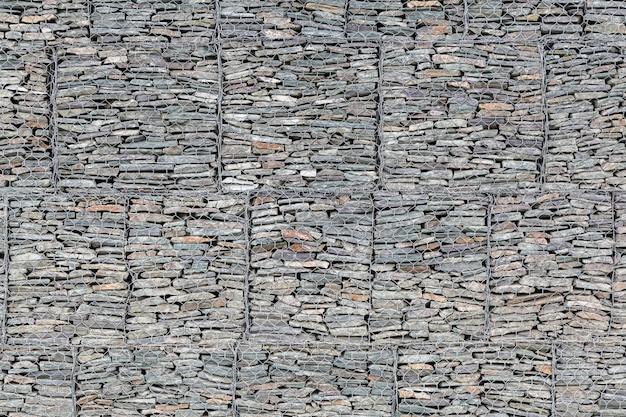 Wand bekleed met kleine grijze stenen achter een metalen rooster