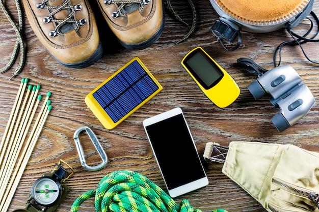 Wandel- of reisuitrusting met laarzen, kompas, verrekijker, lucifers op houten tafel. actieve levensstijl concept.