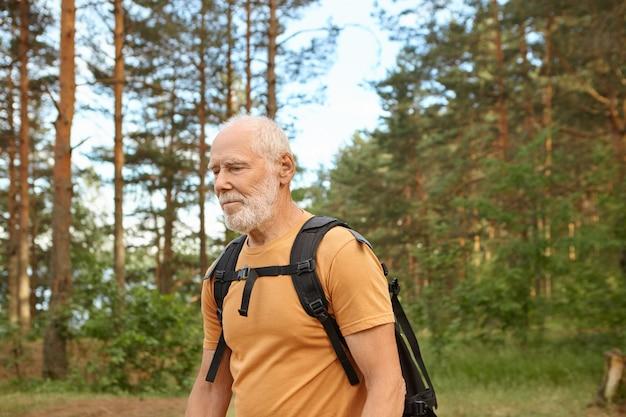 Wandel-, trekking- en avontuurconcept. taille-up foto van knappe energieke senior man met stoppels backpacken in het bos alleen poseren tegen pijnbomen, met zwarte rugzak