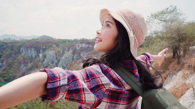 Wandelaar aziatische backpacker vrouw lopen naar de top van de berg, vrouw geniet van haar vakantie op wandelen avontuur gevoel vrijheid.