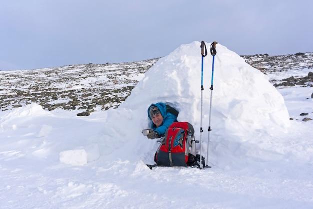 Wandelaar biedt een mok thee aan terwijl hij in een kleine besneeuwde hut-iglo zit