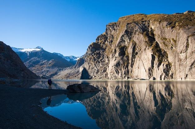 Wandelaar bij douglas glacier terminal lake onder de hellingen van the gladiator, westland tai poutini national park, nieuw-zeeland