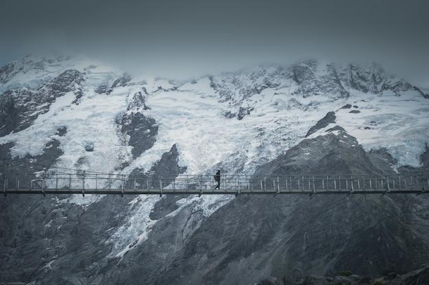 Wandelaar die de brug voor sneeuwberg kruist