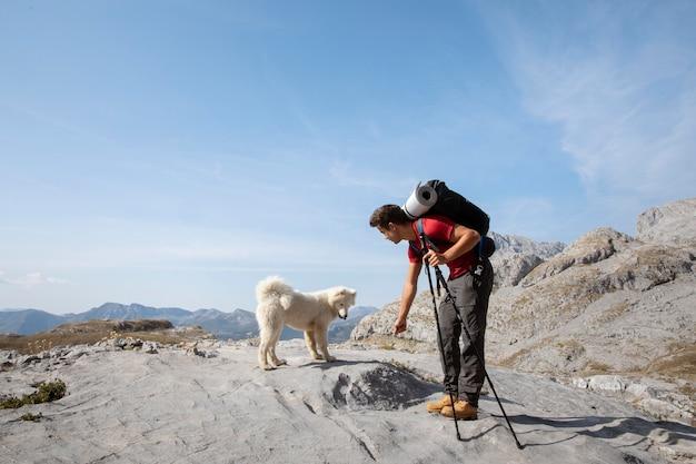 Wandelaar die een schattige witte hond op de bergen sticht
