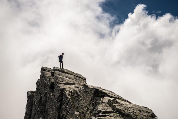 Wandelaar die hoog op rotsachtige bergpiek opstaan
