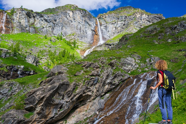 Wandelaar die waterval op berg bekijkt