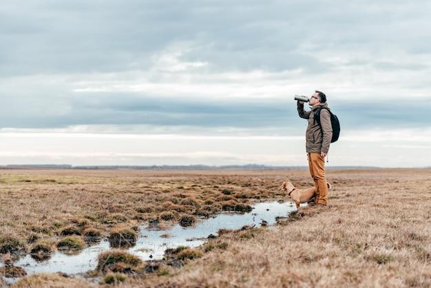 Wandelaar drinkwater bij de vijver