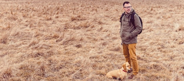 Wandelaar en hond rusten in grasland