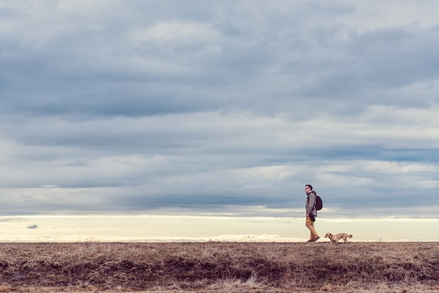 Wandelaar en hond wandelen in grasland
