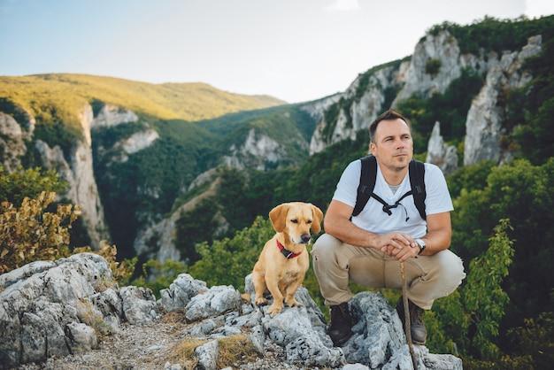 Wandelaar en zijn hond zittend op de bergtop