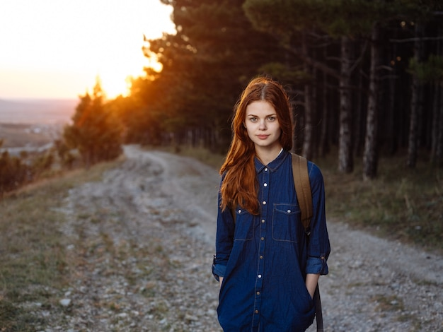 Wandelaar in de bergen met een rugzak op haar rug zonsondergang en bomenaard
