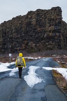 Wandelaar in een gele jas die door de weg loopt, omringd door rotsen en een veld in ijsland