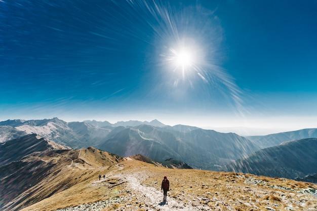 Wandelaar jonge vrouw stijgt naar de top van de berg tegen de achtergrond van de zon en het kruis