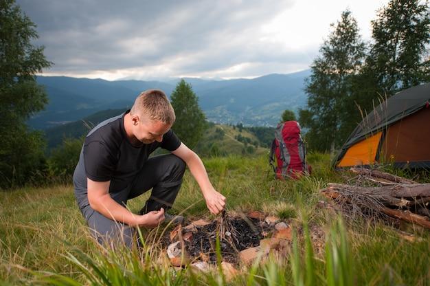 Wandelaar maken van vuur op de heuvel in de buurt van tent