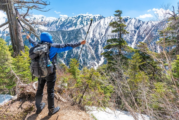 Wandelaar man houdt trekking paal en verspreiden hand wanneer zie sneeuw bergketen op oogpunt.