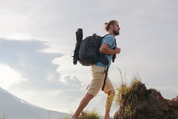 Wandelaar man met rugzak reizen op top vulkaan batur, indonesië