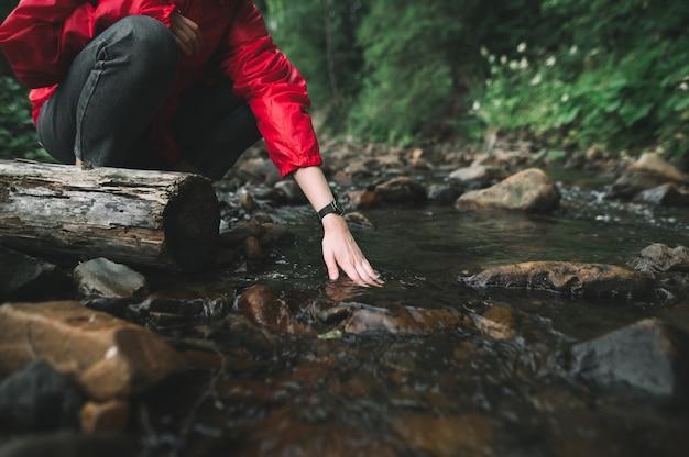 Wandelaar meisje wast haar handen in een bergrivier