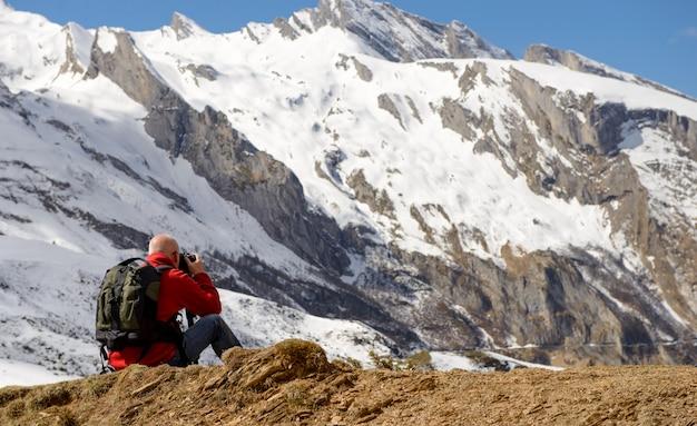 Wandelaar met camera en rugzak die foto van mooie berg nemen