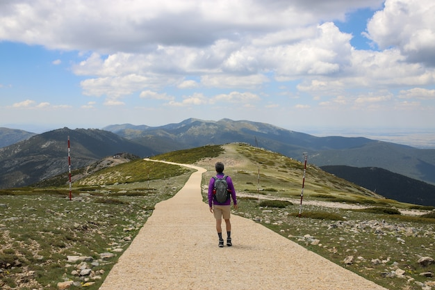 Wandelaar met een rugzak die door een weg loopt op een heuvel bedekt met groen - concept van succes