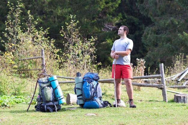 Wandelaar met een rugzak die zich in bergen bevinden die en van valleizicht ontspannen genieten