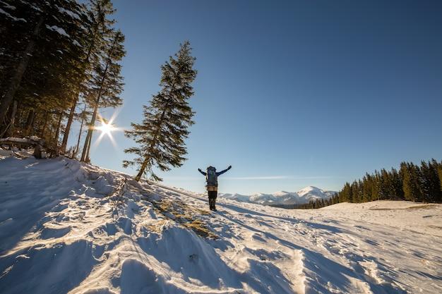 Wandelaar met opgeheven armen staande in de winter sneeuw bedekte natuur landschap genieten van uitzicht op verre besneeuwde bergen.