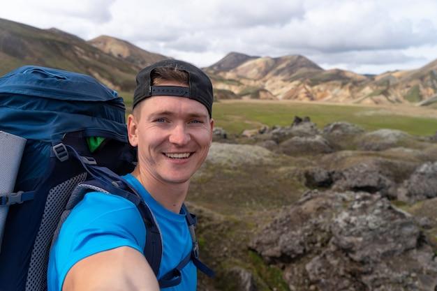 Wandelaar met rugzak die selfie in de landmannalaugar-vallei neemt. ijsland. kleurrijke bergen op het wandelpad laugavegur. de combinatie van lagen veelkleurige rotsen, mineralen, gras en mos.