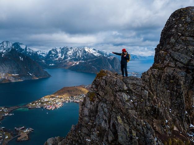 Wandelaar met rugzak die van zonsonderganglandschap geniet in lofoten, noorwegen