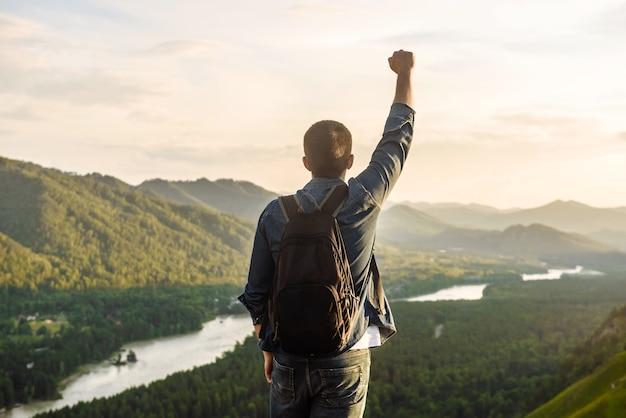 Wandelaar met rugzak staat in de pose van een winnaar met een opgeheven hand op de top van een berg