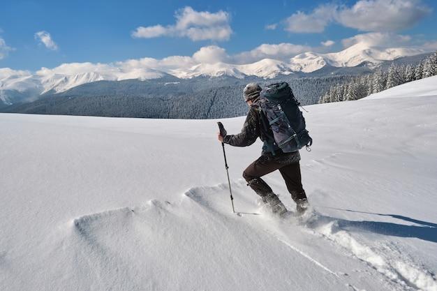 Wandelaar met rugzak wandelen op besneeuwde berghelling op koude winterdag.