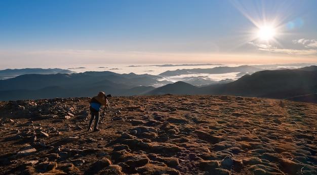 Wandelaar op de bergtop met een camera op een statief