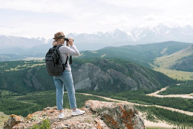 Wandelaar op zoek door verrekijker op de piek van de berg.