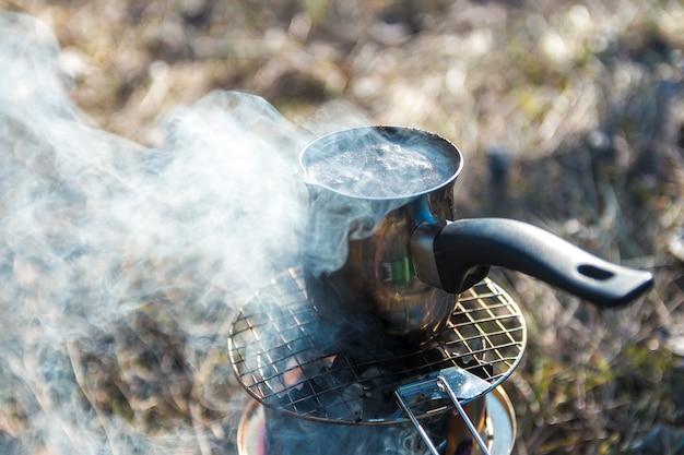 Wandelaar plezier. koffie bereiden op draagbare houtkachel op camping in de bergen