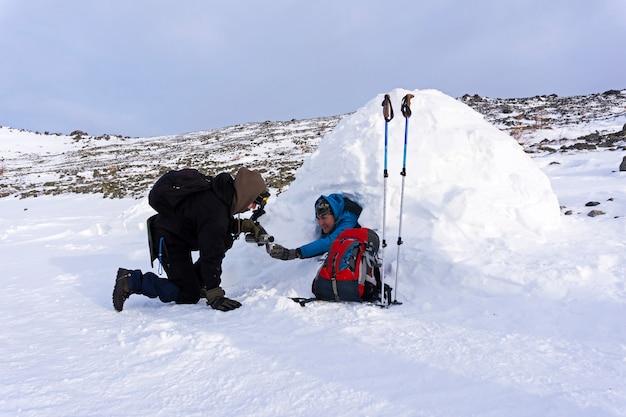 Wandelaar schenkt thee uit de thermoskan naar zijn vriend die in een besneeuwde huisiglo zit