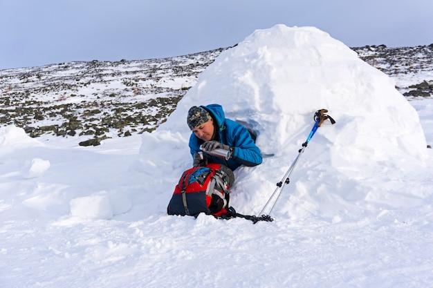 Wandelaar schenkt zichzelf een thee in uit een thermoskan zittend in een besneeuwde huisiglo