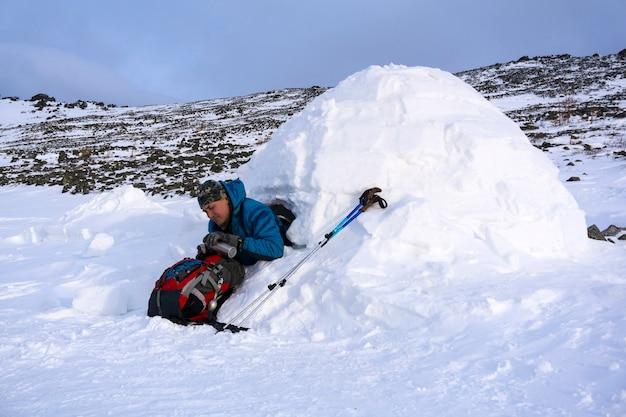 Wandelaar schenkt zichzelf een warme drank in uit een thermoskan zittend in een besneeuwde huisiglo