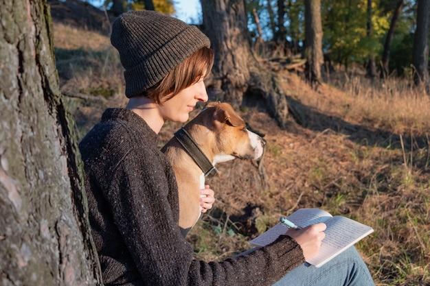 Wandelaar schrijft een dagboek in de prachtige natuur. vrouw geconfronteerd met avondzon maakt aantekeningen in een notitieblok, hond zit naast haar