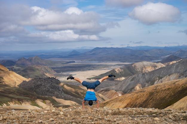 Wandelaar staat op zijn hand in de landmannalaugar-vallei. ijsland. kleurrijke bergen op het wandelpad laugavegur. de combinatie van lagen veelkleurige rotsen, mineralen, gras en mos.