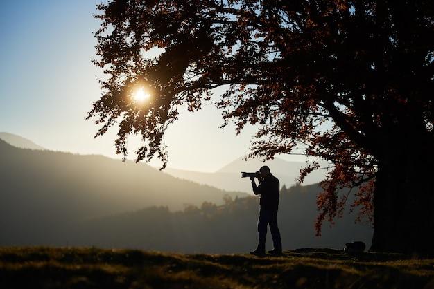 Wandelaar toeristische man met camera op met gras begroeide vallei op achtergrond van berglandschap onder grote boom.