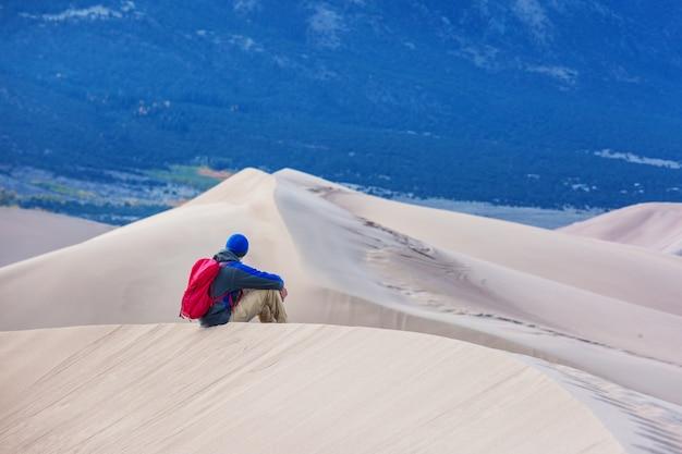 Wandelaar tussen zandduinen in de woestijn
