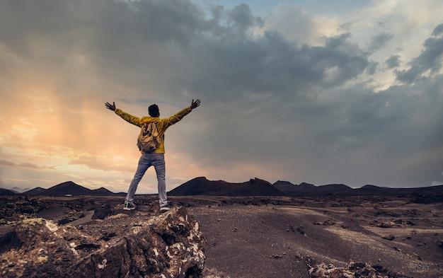 Wandelaar viert succes op de top van een berg bij zonsondergang
