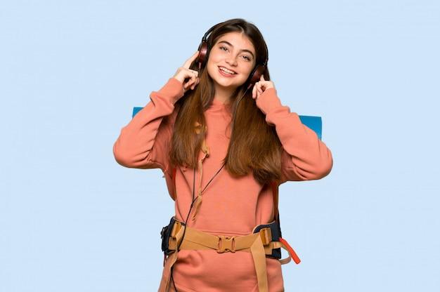 Wandelaarmeisje die aan muziek met hoofdtelefoons op blauw luisteren