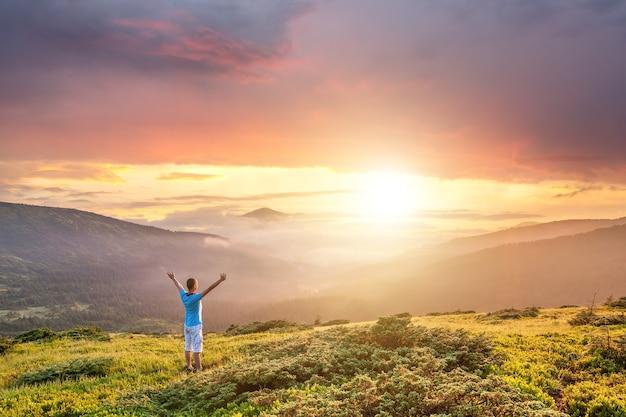 Wandelaarmens die zich bovenop een berg met opgeheven handen bevindt en genietend van warme zonsopgang.