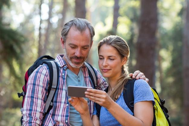 Wandelaarpaar die mobiele telefoon met behulp van
