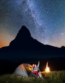 Wandelaars dichtbij kampvuur en gloeiende tent bij nacht onder sterren