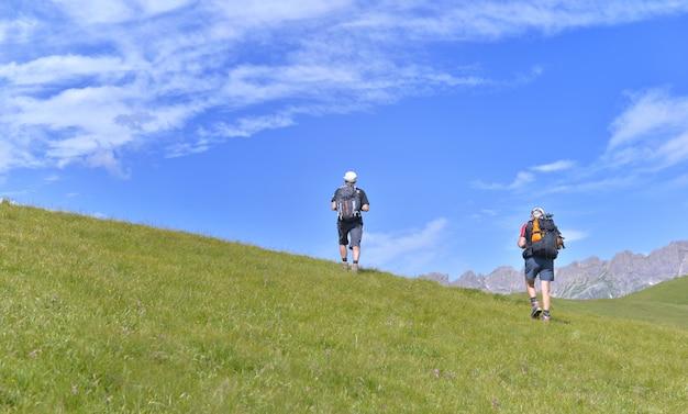 Wandelaars die een grasrijke heuvel in alpiene berg beklimmen onder blauwe hemel