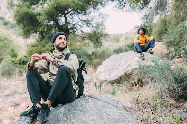 Wandelaars die op rots zitten