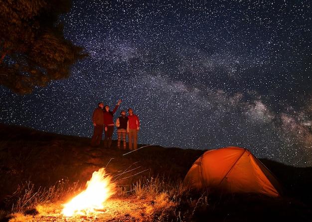 Wandelaars in de buurt van kampvuur en tent 's nachts kamperen
