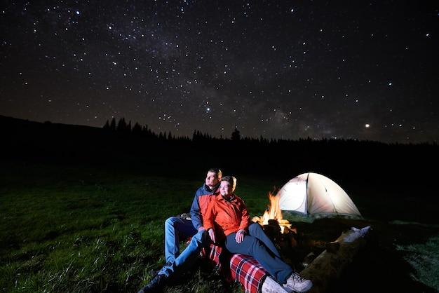 Wandelaars in de buurt van kampvuur en tent 's nachts
