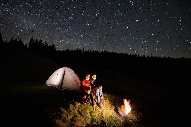 Wandelaars in de buurt van kampvuur en toeristentent 's nachts